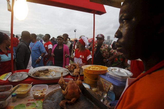 A cook stands in front of his goods during the Festival des Grillades, in the yard of the Culture Palace of Abidjan, September 5, 2015. (Photo by Luc Gnago/Reuters)