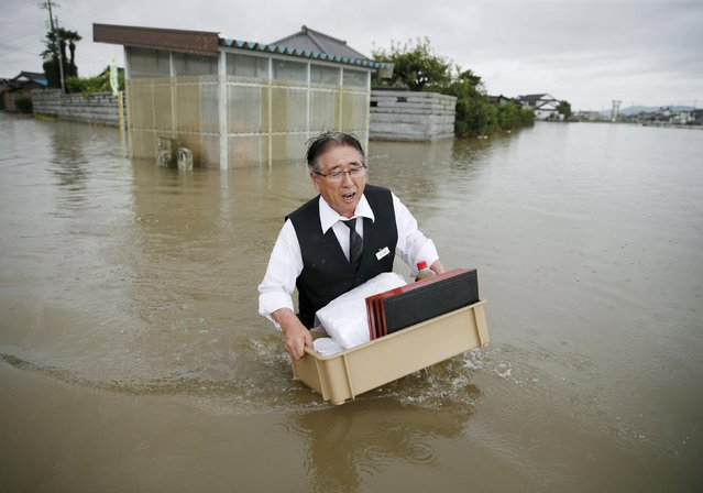 A man holding a tray of belongings wades through a road at an area flooded by the Omoigawa river, caused by typhoon Etau in Oyama, Tochigi prefecture, Japan, in this photo taken by Kyodo September 10, 2015. (Photo by Reuters/Kyodo News)