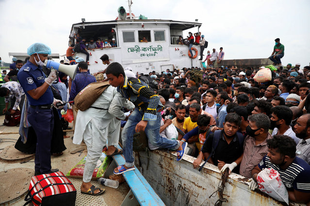 A police officer urges migrants who are trying to go home to celebrate Eid al-Fitr, to get off from an overcrowded ferry, after a boat capsized, amid concerns over the coronavirus disease (COVID-19) outbreak, in Munshiganj, Bangladesh, May 19, 2020. (Photo by Mohammad Ponir Hossain/Reuters)