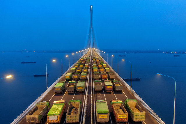 This aerial photo taken on May 27, 2020 shows trucks driving on the Hutong Yangtze River Bridge during a load test in Nantong, in China's eastern Jiangsu province. (Photo by AFP Photo/China Stringer Network)