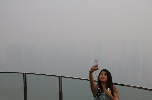 A woman takes a selfie with the skyline of the central business district shrouded by haze in Singapore September 14, 2015. (Photo by Edgar Su/Reuters)