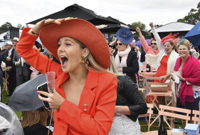 A racegoers cheers on her horse in Race 4 ahead of the race of the Melbourne Cup at Flemington Racecourse in Melbourne, Australia, Tuesday, November 7, 2017. (Photo by Andy Brownbill/AP Photo)