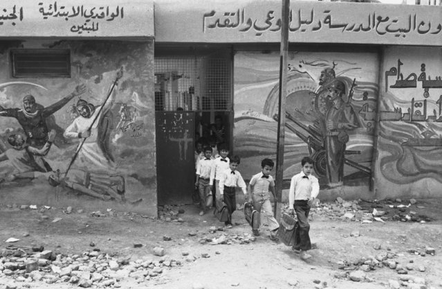 In this April 28, 1984 file photo, elementary school pupils, dressed in the standard white shirt school uniform of Iraq, leave their school in Baghdad. Scenes on the wall depict the Iraq-Iran war as a new battle between Arabia and Persia. The Iran-Iraq war launched by Iraq's Saddam Hussein after the Iranian revolution resulted in around half a million deaths. A generation was decimated in both countries. (Photo by Herve Merliac/AP Photo)
