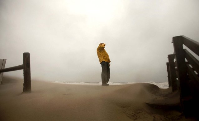 Matt Francis holds onto his hat as the wind-driven sand and rain from Hurricane Sandy blows across the beaches of Sandbridge in Virginia Beach. (Photo by L. Todd Spencer/The Virginian-Pilot)
