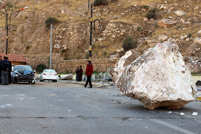 An Iraqi Kurdish man walks by a large rock which fell from the top of a mountain during the earthquake that hit Darbandikhan town, near Sulaymaniya city, northern Iraq on 13 November 2017. At least six people were killed and 50 others injured in Iraqi Kurdistan's Sulaymaniyah when a powerful magnitude 7.2 earthquake hit the region along the border between Iran and Iraq on 12 November, local officials said. At least 328 inhabitants were killed and another 3,950 injured in Iran's Kermanshah province bordering Iraq. (Photo by Afan Abdulkhaleq/EPA/EFE)