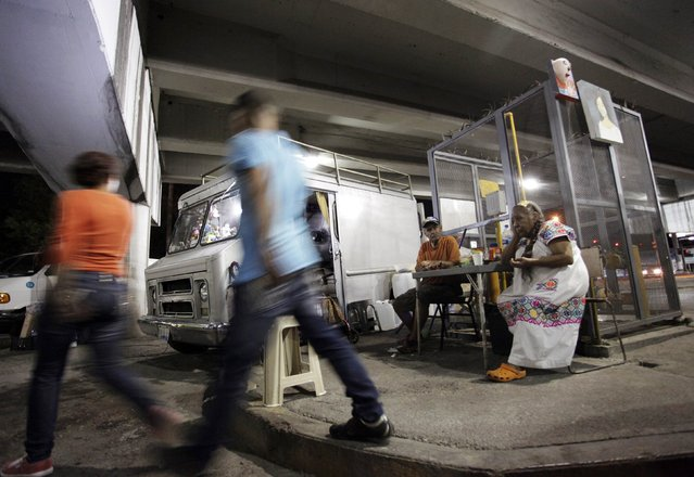 People walk past Modesto Sotero (2nd R), 82, and his wife Maria Josefina Perez (R), 81, sitting together outside the truck they have been living in for the last nine years underneath a bridge in Monterrey, Mexico, on September 29, 2014. (Photo by Daniel Becerril/Reuters)