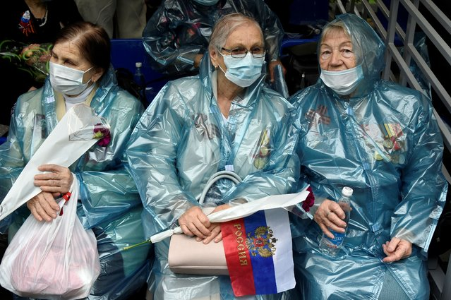 People wearing face masks to protect against the coronavirus, watch the Victory Day military parade marking the 75th anniversary of the Nazi defeat in World War II, in Sevastopol, Crimea, Wednesday, June 24, 2020. (Photo by AP Photo/Stringer)