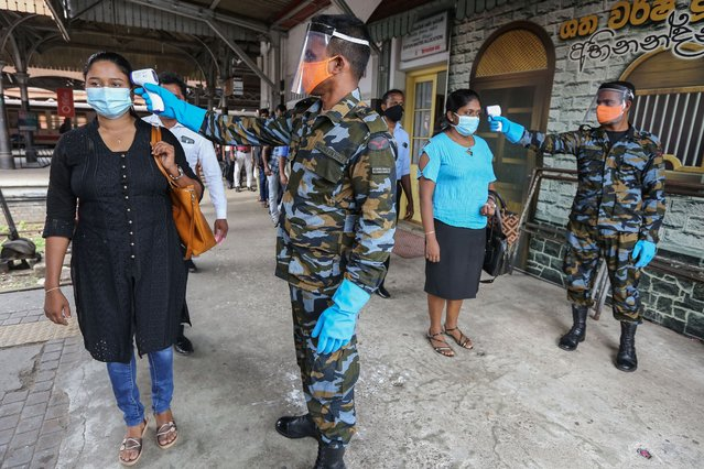 Sri Lankan Airforce soldiers check the body temperature of passengers at the fort main railway station in Colombo, Sri Lanka, 26 May 2020. The Sri Lankan government announced on May 26 that an island-wide day time curfew would be lifted to restart the country's economic activities. The curfew was imposed for nearly two-month in order to slow down the spread of the SARS-CoV-2 coronavirus that causes the COVID-19 disease. (Photo by Chamila Karunarathne/EPA/EFE/Rex Features/Shutterstock)
