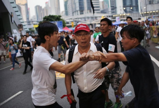 Pro-democracy protesters argue with a man (C) as he walks away from an area blocked by protesters outside the government headquarters office in Hong Kong October 9, 2014. Democratic lawmakers in Hong Kong demanded anti-graft officers investigate a $6.4 million business payout to Chief Executive Leung Chun-ying on Thursday, as political fallout grows from massive student-led protests calling for democracy in the Chinese-controlled city. (Photo by Carlos Barria/Reuters)