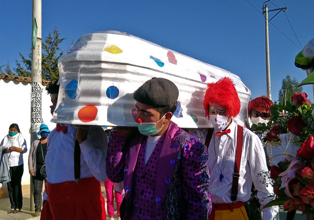 "Admirers of Peruvian clown William Rojas, known professionally as ""Chupetin"", carry his coffin during his funeral procession to the Eternal Hope cemetery in Huancayo, Peru, on July 2, 2020. Rojas, 45, died from COVID-19 after five days of being in intensive care. Peru surpassed 10,000 deaths from the coronavirus on Thursday, the health ministry said, a day after the government began easing a national lockdown in a bid to revive the economy. (Photo by Pedro Tinoco/AFP Photo)"