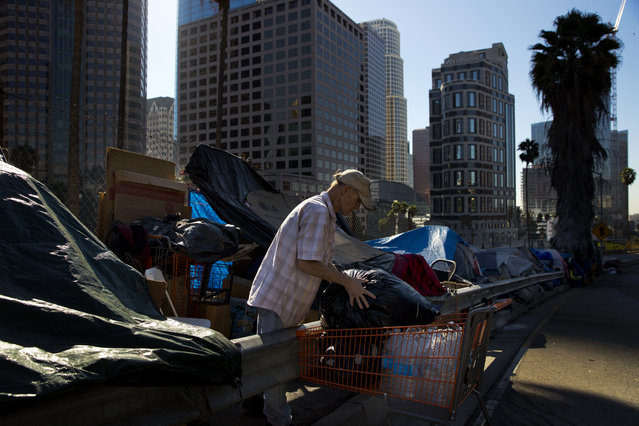 "A man who identified himself just as Vincent, sorts his belongings outside his tent Friday, December 1, 2017, in Los Angeles. Vincent said he thought he was bulletproof and never had to worry about getting a job as a young man. ""Things ain't the way they were anymore"". (Photo by Jae C. Hong/AP Photo)"