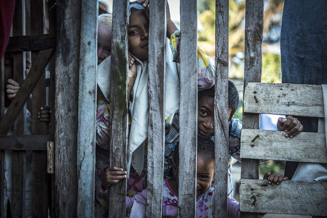 A picture made available on 24 September 2015 of children peeping through a picket fence outside their home in Fort Dauphin, Madagascar, 23 September 2015. Madagascar is one of the poorest countries in the world and small markets in towns and villages is one of the main financial drivers in the countries economy. (Photo by Shiraaz Mohamed/EPA)