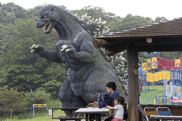 A family sit on a bench near a Godzilla's slide at Kurihama flower park in Yokosuka, near Tokyo Wednesday, July 15, 2020. (Photo by Koji Sasahara/AP Photo)