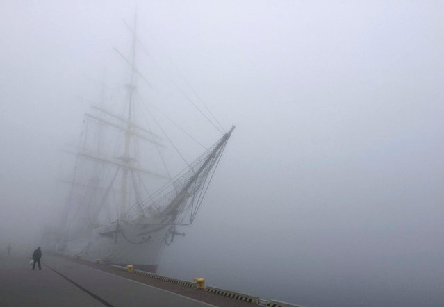 A man walks past Dar Pomorza (Gift of Pomerania), a full-rigged sailing ship, now a museum, as thick fog covers the Port of Gdynia, Poland April 4, 2017. (Photo by Radu Sigheti/Reuters)