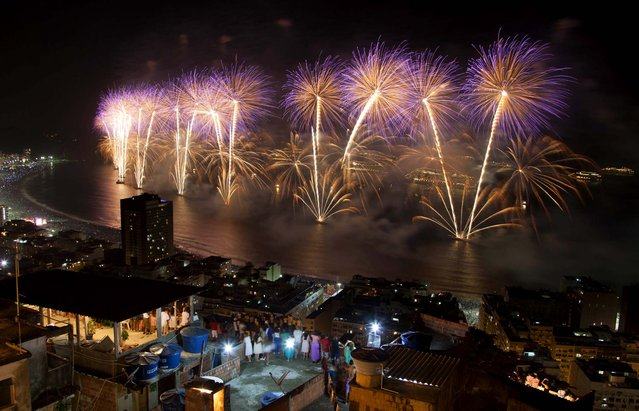 People watch fireworks exploding over Copacabana beach during New Year celebrations in the Pavao Pavaozinho slum in Rio de Janeiro. (Photo by Felipe Dana/Associated Press)