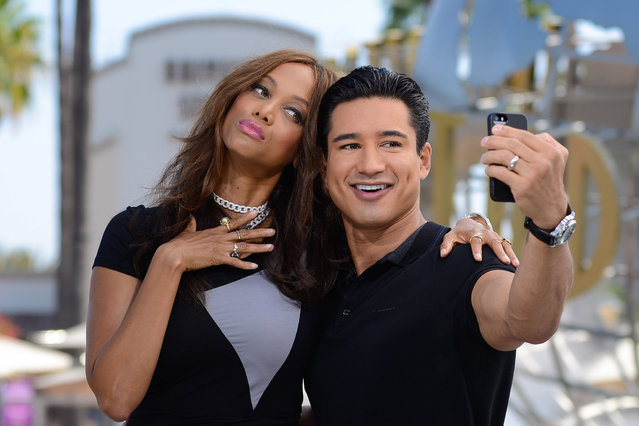 "Tyra Banks and Mario Lopez take a selfie at ""Extra"" at Universal Studios Hollywood on August 20, 2014 in Universal City, California. (Photo by Noel Vasquez/Getty Images)"