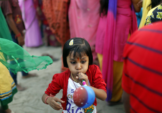 A girl blows a balloon pipe during the Hindu religious festival of Chatt Puja in New Delhi October 29, 2014. (Photo by Anindito Mukherjee/Reuters)