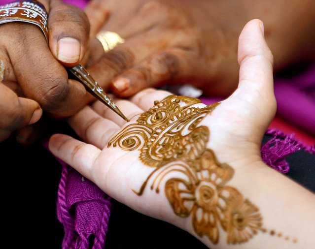 A girl applies henna on a hand of a customer at a stall ahead of Eid al-Adha in Colombo, Sri Lanka September 10, 2016. (Photo by Dinuka Liyanawatte/Reuters)