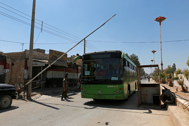 A bus carrying people to be evacuated in Daraya passes a Syrian Army checkpoint, after reports of an agreement between rebels and Syria's army to evacuate civilians and rebel fighters from Moadamiya, in Damascus, Syria September 2, 2016. (Photo by Omar Sanadiki/Reuters)