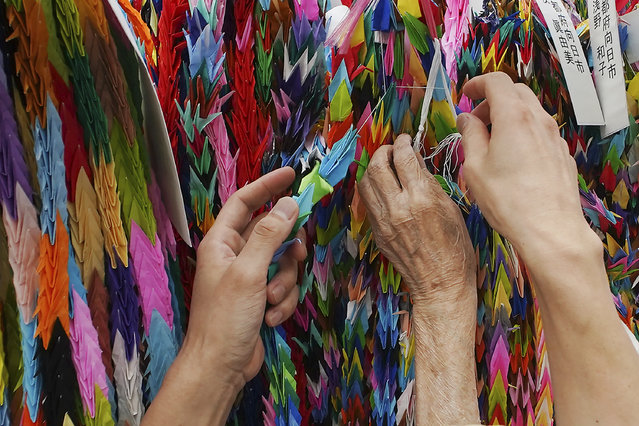 Hatsue Onda, center, is helped by Kengo Onda to offer strings of colorful paper cranes to the victims of the 1945 Atomic bombing near Hiroshima Peace Memorial Museum in Hiroshima, western Japan, Monday, August 3, 2020. The origami cranes that can be seen throughout the city became a symbol of peace because of atomic bomb survivor Sadako Sasaki, who, while battling leukemia, folded similar cranes using medicine wrappers after hearing an old Japanese story that those who fold a thousand cranes are granted one wish. (Photo by Eugene Hoshiko/AP Photo)