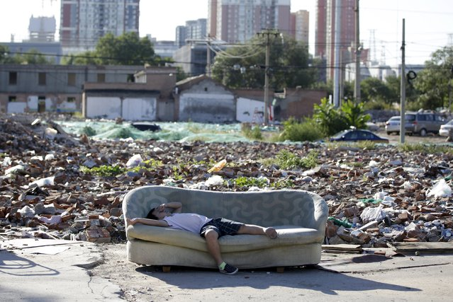 A boy takes a nap on a disused sofa near Chinese artist ROBBBB's works in the ruins of houses which were pulled down, in Beijing September 25, 2015. (Photo by Jason Lee/Reuters)