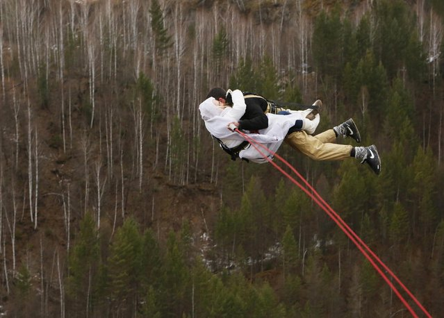 """A newly married couple, members of the amateur rope-jumping group """"Exit Point"""", jumps from a 44-metre high (144-ft) water pipe bridge in the Siberian Taiga area outside Krasnoyarsk, November 2, 2014. Rope-jumping, an extreme sport, involves jumping from a high point using an advanced leverage system combining mountaineering and rope safety equipment. (Photo by Ilya Naymushin/Reuters)"""