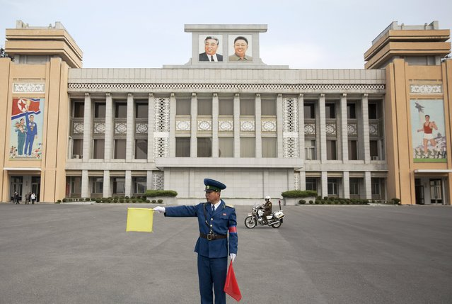 A policeman directs traffic at the Kim Il Sung Stadium before North Korea's preliminary 2018 World Cup and 2019 AFC Asian Cup qualifying soccer match against Philippines in Pyongyang October 8, 2015. (Photo by Damir Sagolj/Reuters)