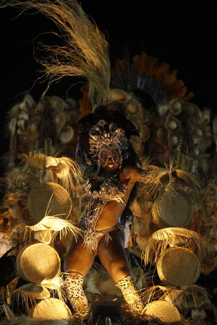 A reveller from Uniao de Jacarepagua samba school dances atop a float during the second night of the A Group annual Carnival parade in Rio de Janeiro's Sambadrome February 9, 2013. The samba school which wins the A Group will parade with the top samba groups at the Special Group performance in 2014. (Photo by Pilar Olivares/Reuters)