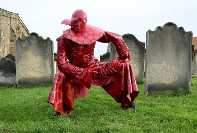 """Catasta"" wearing a latex hexus costume poses in the grounds of St Mary's Church during the ""Whitby Goth Weekend"", North Yorkshire, on November 2, 2014. (Photo by Anna Gowthorpe/PA Wire)"