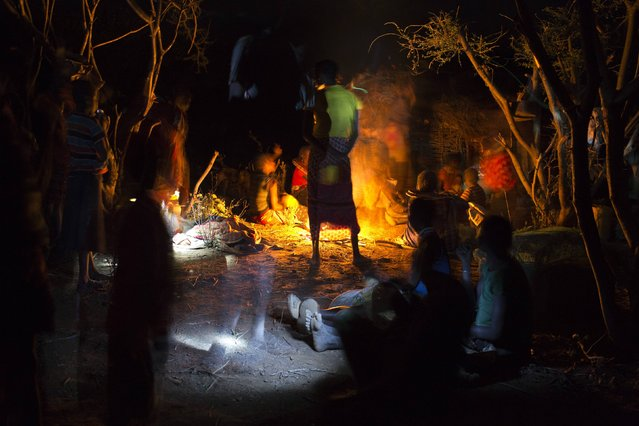 Members of the Pokot tribe gather round a fire before a female circumcision ceremony, about 80 kilometres from the town of Marigat in Baringo County, October 16, 2014. (Photo by Siegfried Modola/Reuters)