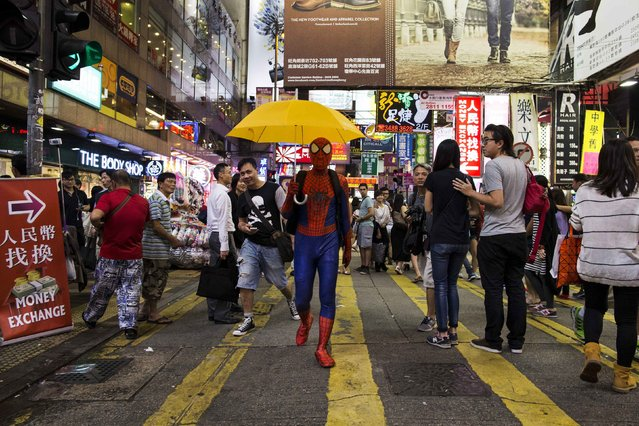 A pro-democracy supporter dressed as comic book character Spider-Man carries a yellow umbrella, regarded a symbol of the Occupy civil disobedience movement, on a road blocked by protesters at Mongkok shopping district in Hong Kong October 24, 2014. (Photo by Tyrone Siu/Reuters)