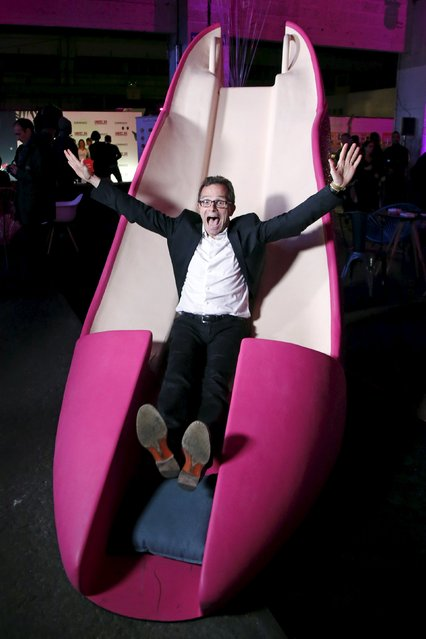 Stephane Treppoz, CEO of Sarenza, slides on a giant high heel model in Paris, France, October 15, 2015. (Photo by Charles Platiau/Reuters)