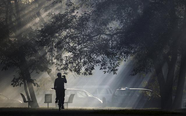 "A cyclist films smoke from an art installation by artist Fabian Knecht beside the ""Neue Nationalgalerie"" gallery in Berlin November 1, 2014. (Photo by Hannibal Hanschke/Reuters)"