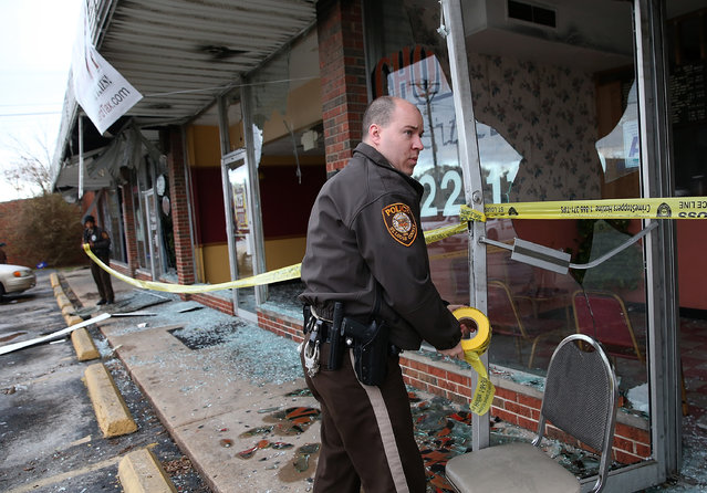 A St. Louis county police officer uses police tape to secure a building that eas burned during a demonstration on November 25, 2014 in Dellwood, Missouri. (Photo by Justin Sullivan/Getty Images)