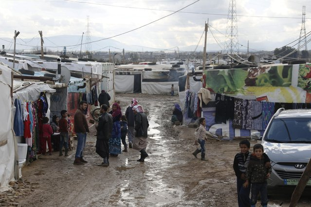 Syrian refugees stand on muddy ground at a refugee camp in Zahle in the Bekaa valley November 27, 2014. (Photo by Jamal Saidi/Reuters)