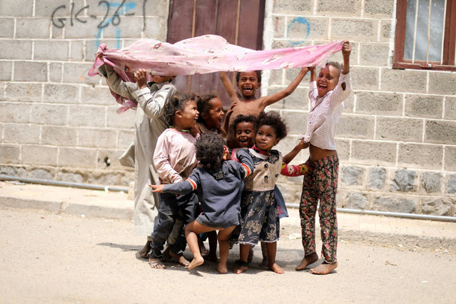 Children from the Muhamasheen (marginalized) community play outside at their neighbourhood in Sanaa, Yemen on July 18, 2020. (Photo by Khaled Abdullah/Reuters)