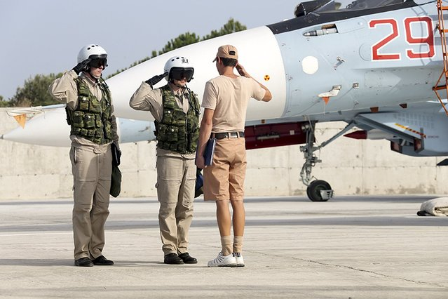 A ground crew member reports to pilots that their Sukhoi Su-30 fighter jet is ready for a combat mission at Hmeymim air base near Latakia, Syria, in this handout photograph released by Russia's Defence Ministry, October 22, 2015. (Photo by Reuters/Ministry of Defence of the Russian Federation)