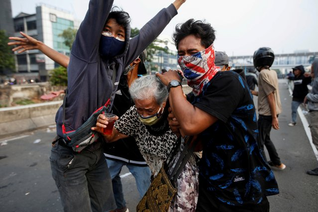 Demonstrators cover an elderly woman during clashes with police, as they protest against the government's labour reforms in a controversial jobs creation law in Jakarta, Indonesia, October 8, 2020. (Photo by Willy Kurniawan/Reuters)