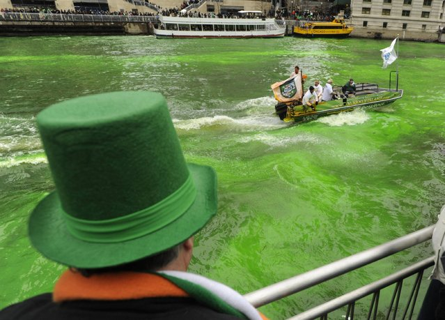 A spectator looks on as the Chicago River is dyed green ahead of the St. Patrick's Day parade in Chicago, Saturday, March, 16, 2013. With the holiday itself falling on a Sunday, many celebrations were scheduled  for Saturday because of religious observances. (Photo by Paul Beaty/AP Photo)