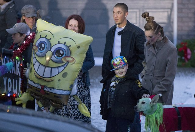 Evan Leversage, who is terminally ill with brain cancer, is greeted by a Christmas decorated dog as he stands with his mother Nicole Wellwood (C, partially obscured by the balloon), and his father Travis Leversage (2nd R) in St. George, Ontario, Canada October 24, 2015. (Photo by Mark Blinch/Reuters)