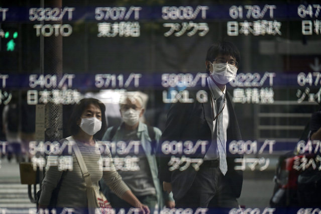 People are reflected on a blank electronic stock board supposedly showing Japan's Nikkei 225 index at a securities firm Thursday, October 1, 2020, in Tokyo. Trading on the Tokyo Stock Exchange was suspended Thursday because of a problem in the system for relaying market information. Most other Asian markets were closed for national holidays. (Photo by Eugene Hoshiko/AP Photo)