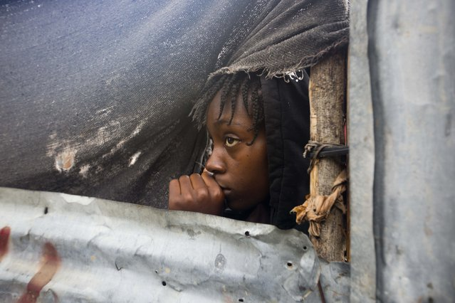 A girl watches as the authorities arrive to evacuate people from her house in Tabarre, Haiti, Monday, October 3, 2016. (Photo by Dieu Nalio Chery/AP Photo)