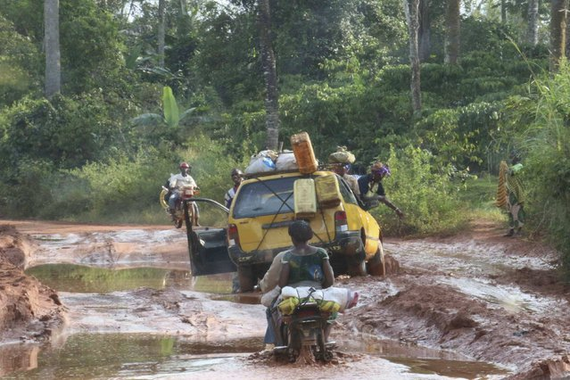 Vehicles drive through a muddy road outside Beyla, Guinea, November 25, 2014. (Photo by Fabien Offner/Reuters)