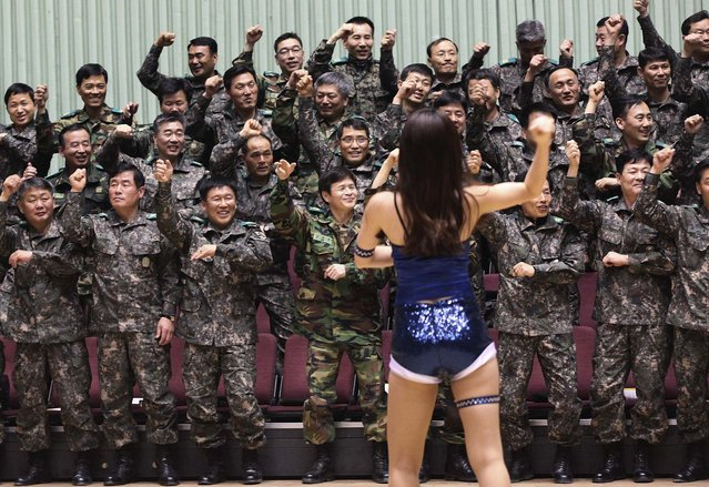 """South Korean army reservists perform PSY's """"Gangnam Style"""" dance with a cheerleader before their Foundation Day ceremony at a gymnasium in Seoul, on April 5, 2013. (Photo by Ahn Young-joon/Associated Press)"""