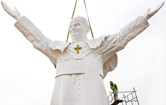 A worker adds finishing touches to a giant statue  of the late Pope John Paul II  for the unveiling this weekend, in Czestochowa, Poland, on April 9, 2013. The 45 foot fiberglass figure will tower over the city that is home to Poland's most important Catholic pilgrimage site, Jasna Gora. Funded by a private investor, the pontiff appears smiling and stretching his arms to the world.  (Photo by Czarek Sokolowski/Associated Press)