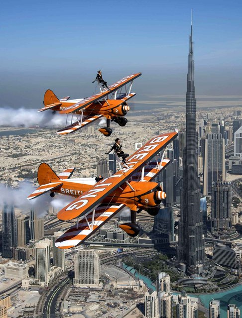 The British Breitling Wingwalkers, Danielle Hughes and Emily Guilding, fly past the Burj Khalifa, the world's tallest man-made structure, in Dubai at 2,000 feet (610 meters) in excess of 100mp/h, ahead of their Dubai debut performance at the 2014 UIM Skydive Dubai XCAT World Powerboating Series, on Saturday, 13th December 2014. (Photo by Katsuhiko Tokunaga/Breitling via AP Images)