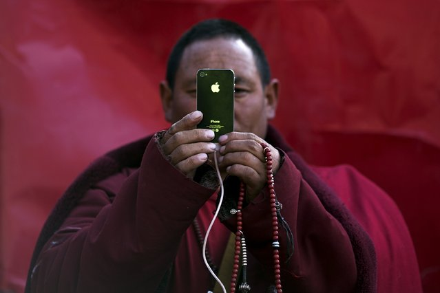 A Tibetan Buddhist monk take pictures with his smartphone of a daily chanting session at a Buddhist laymen lodge during the Utmost Bliss Dharma Assembly, the last of the four Dharma assemblies at Larung Wuming Buddhist Institute in remote Sertar county, Garze Tibetan Autonomous Prefecture, Sichuan province, China early October 30, 2015. (Photo by Damir Sagolj/Reuters)