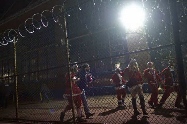 "People in Santa Claus outfits attend an after-party for the ""Running of the Santas"" behind a barbed wire fence at the Electric Factory in Philadelphia, Pennsylvania December 13, 2014. (Photo by Mark Makela/Reuters)"