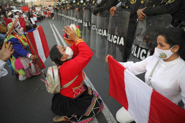 Local folk artists perform next to a police line outside the Congress building, as they wait for news from inside on who will be the country's next president, in Lima, Peru, Sunday, November 15, 2020. (Photo by Rodrigo Abd/AP Photo)