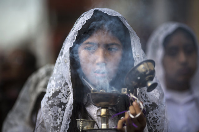 A girl burns incense while taking part in a Holy Week procession in Lima, Peru, Sunday, April 1, 2018. Processions take place throughout Peru during the Easter Holy Week. (Photo by Rodrigo Abd/AP Photo)